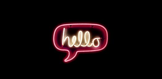 """Rosa neonskylt i form av en pratbubbla med texten """"Hello"""" skrivet i mitten"""